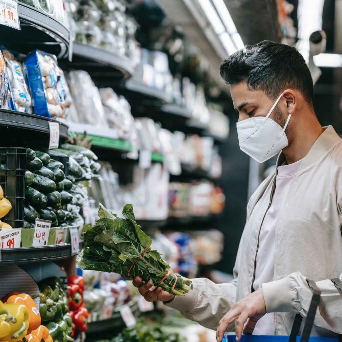 young ethnic guy buying bunch of fresh spinach in supermarket