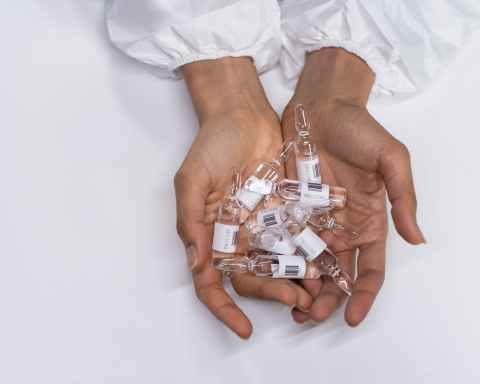 vaccine vials on womans hands