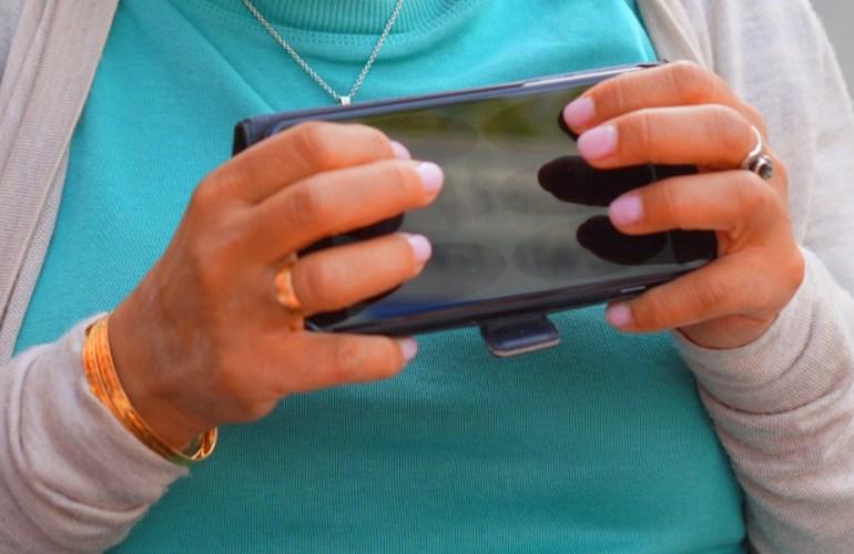 Lydia sitzt im Cafe draußen und schreibt Braille auf dem iPhone