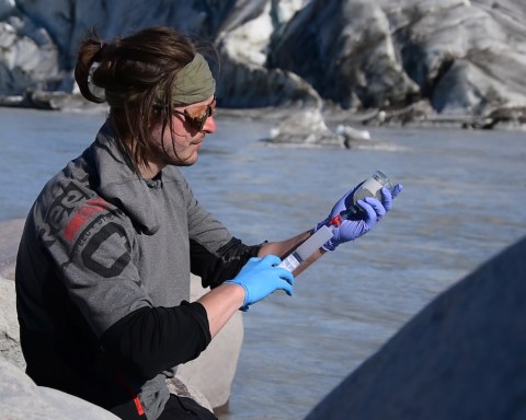 Prélèvement d'échantillon d'eau de fonte au Groenland par Guillaume Lamarche-Gagnon. © Marie Bulinova