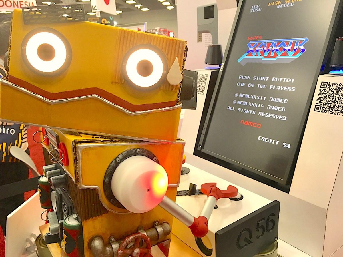 """Avec sa tête en carton, le robot """"AI gamer"""" joue seul devant sa console et compte sur l'intelligence artificielle pour progresser dans le jeu... Illusion?"""
