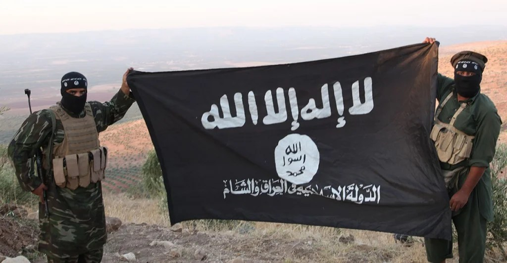 "ISIS fighters holding the Al-Qaeda flag with ""Islamic State of Iraq and the Levant"" written on it. (Photo: Medyan Dairieh/Newscom)"