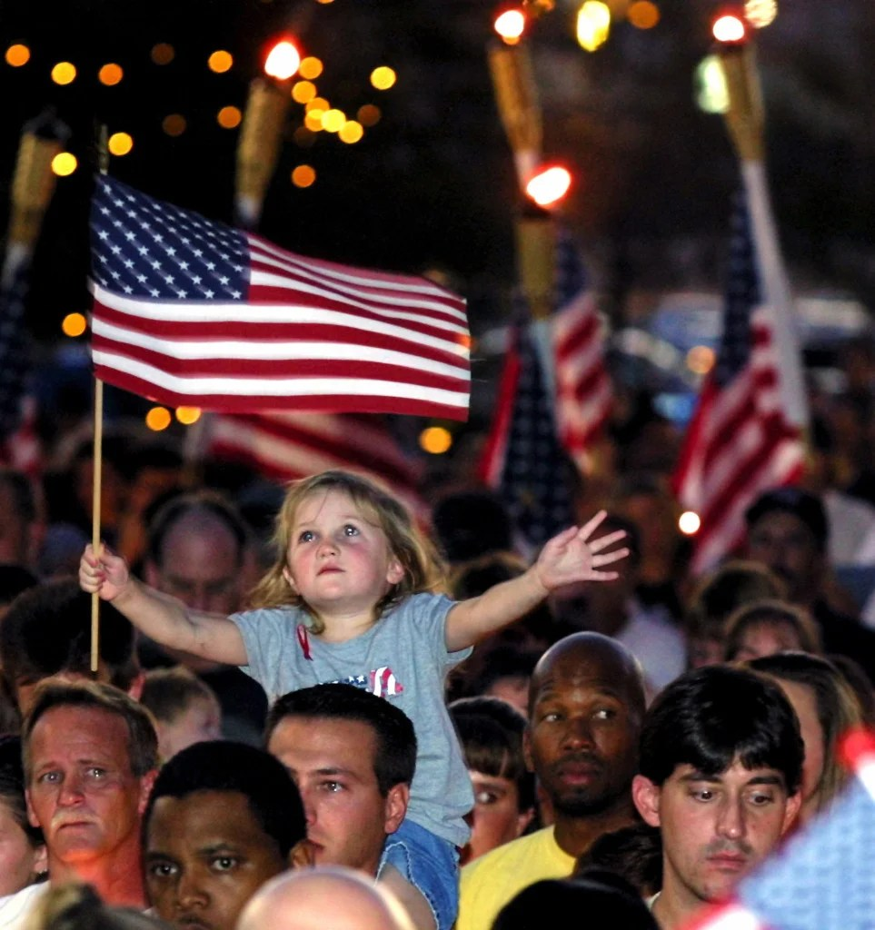 Four-year-old Alana Milawski waves an American flag as she sits on her father's shoulders during a candlelight vigil held in Las Vegas' Thomas & Mack Center on the campus of the University of Nevada-Las Vegas September 12, 2001. (Photo: REUTERS/Ethan Miller/Newscom)