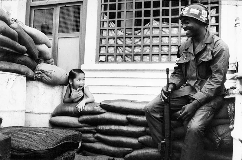 An American sentry seats guard in a street of Saigon, holding a gun in his hand with a curious new friend. (Photo: monhistorypix/Newscom)