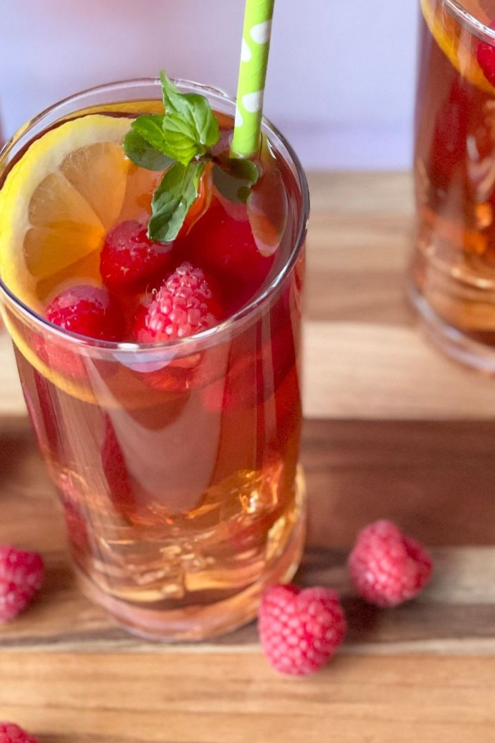 raspberry iced tea in glass with lemon slices, fresh raspberries, and straw