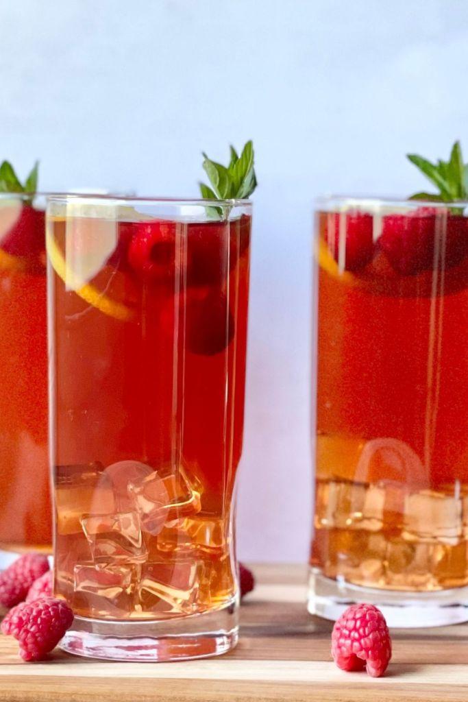 raspberry iced tea in glass with lemon slices, fresh raspberries, and straw