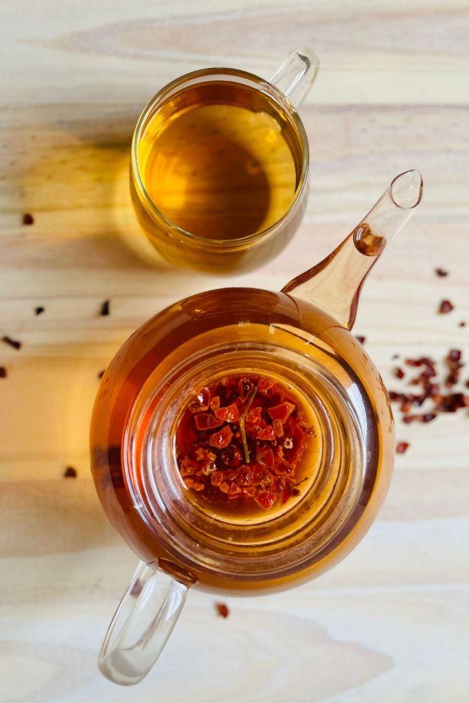 loose rose hip tea in teapot with tea cup
