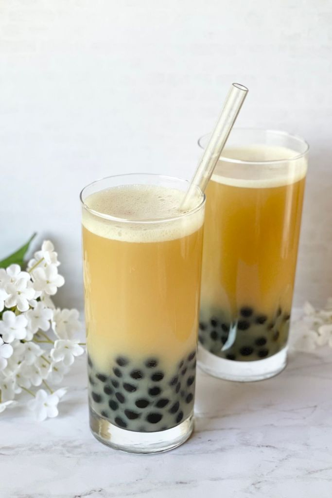 jasmine green milk tea with honey boba, straw and flowers