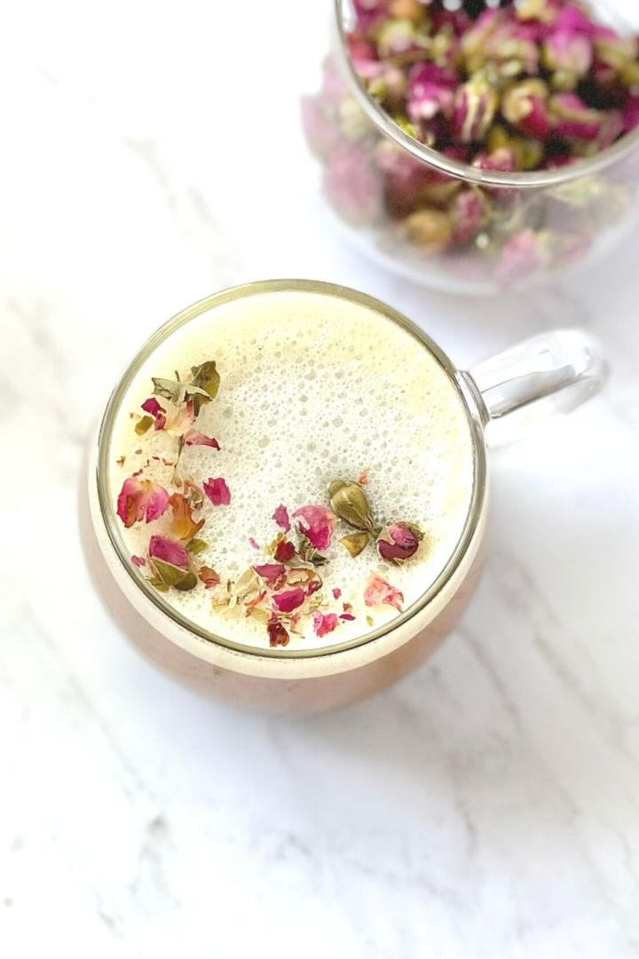 rose milk tea in cup, cup filled with rosebuds