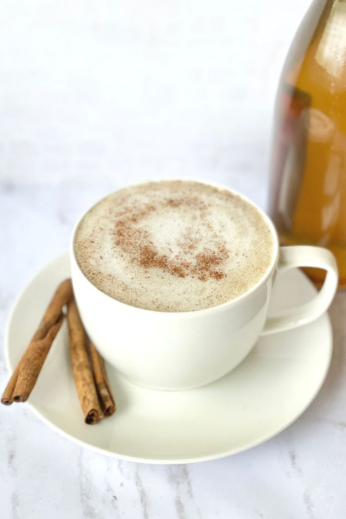 chai tea latte in cup with saucer, and cinnamon sticks