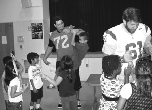 Big brother · USC football players Kristofer O'Dowd and Martin Coleman teach local school children about unconventional learning. - Photo courtesy of SOS Classroom
