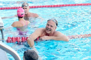 Just keep swimming · Olympian John Naber shakes the hand of a fellow relay participant during the 34th annual Swim with Mike swim-a-thon, which took place at the Uytengsu Aquatics Center on April 5. - Kirstin Louie | Daily Trojan