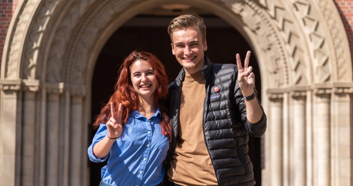 """Rose Ritch stands on the left in a blue button-up shirt. Truman Fritz stands on the right in a dark khaki brown shirt and black jacket. Both are smiling as they throw up the """"Fight On!"""" symbol. They stand in front of Bovard Auditorium on a sunny day."""