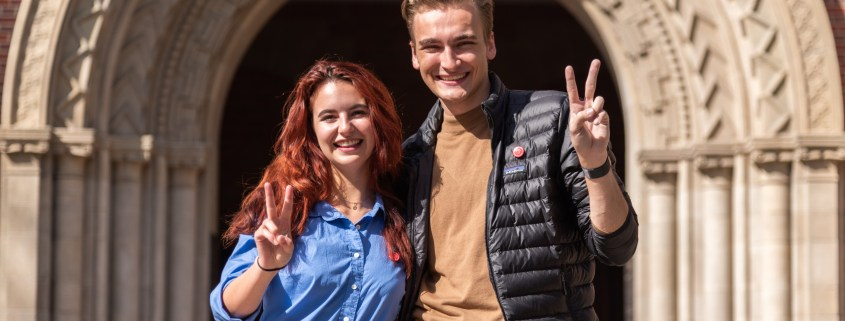 "Rose Ritch stands on the left in a blue button-up shirt. Truman Fritz stands on the right in a dark khaki brown shirt and black jacket. Both are smiling as they throw up the ""Fight On!"" symbol. They stand in front of Bovard Auditorium on a sunny day."