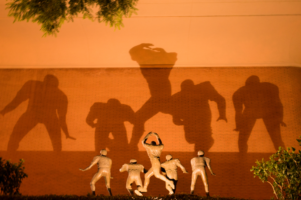 "Statues of USC's 1969 defensive line, known as ""The Wild Bunch,"" cast a shadow outside of Heritage Hall."