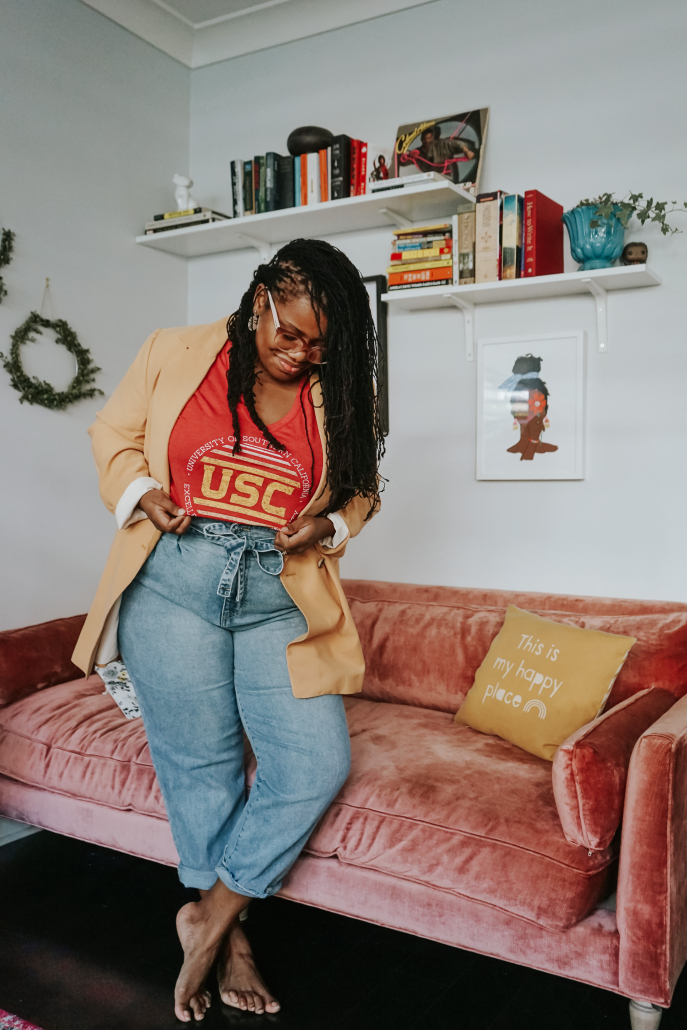 Samantha Broxton poses with a bright red USC shirt, paired with a tan jacket and light blue jeans. Broxton is looking down toward the shirt. In the background, two bookcases showcase various books and mementos with two photo frames below.