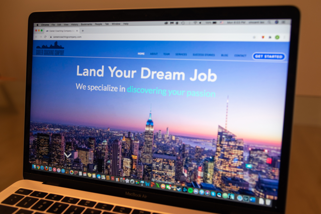 "A side angle photo of a MacBook Air with the screen displaying the landing page of the website www.careercoachingcomapny.com. The page reads the words ""Land Your Dream Job"" in white text and the background is a photo of the Empire State Building and many other lit up buildings during sunset. The company's logo is in the top right corner and the top is the menu bar including eight tabs including some that read ""About,"" ""Services"" and ""Contact."""