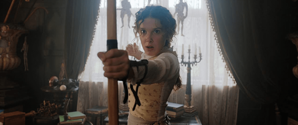 "Millie Bobby Brown starring as Enola Holmes in Netflix's ""Enola Holmes"" draws a bow and arrow in side a Victorian house."
