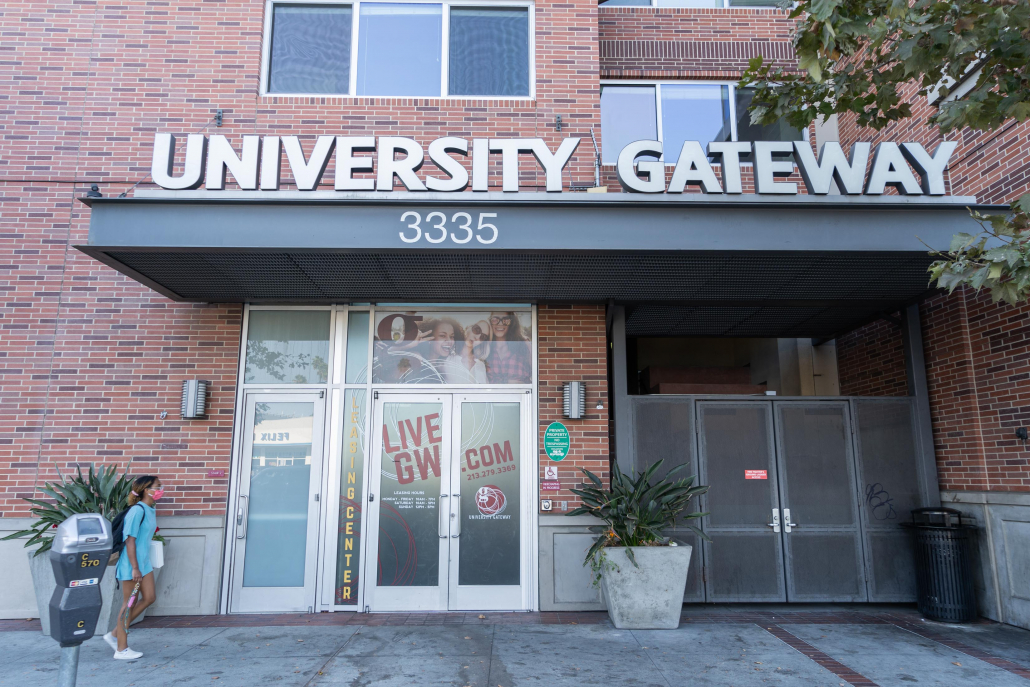 "An image of the Gateway Apartments entrance with a gray sign reading ""University Gateway."""