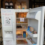"Photo of a stocked fridge with various food items including a variety of vegetables and bags of trail mix. On the closed fridge door marker scripted words read ""Free Food!!"" and ""Take what you need."""