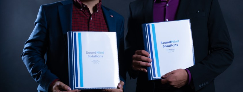 "Photo of Brian Femminella and Travis Chen holding binders that read ""SoundMind Solutions."""