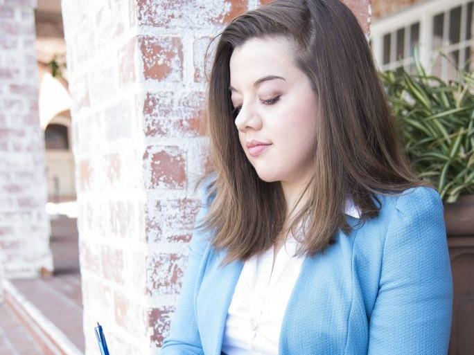 Geanna Culbertson sits on brick steps while signing a blue hardback novel.