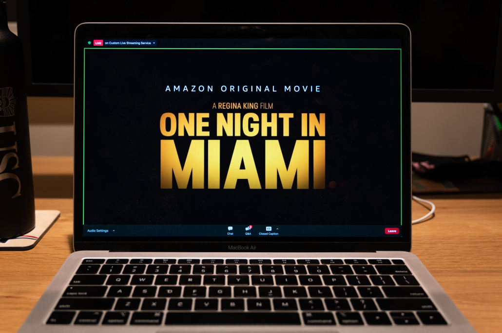 """A colored photograph of a laptop sitting at a table reading """"One Night in Miami"""""""