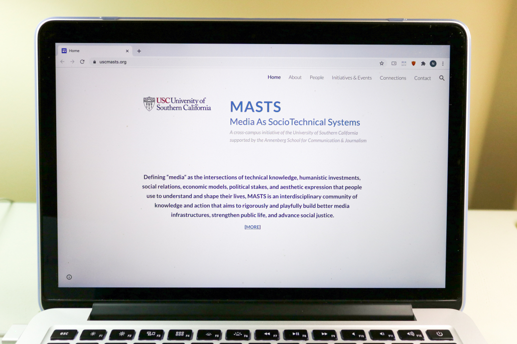 A laptop screen is open to the MASTS website which has a description of what the group is.