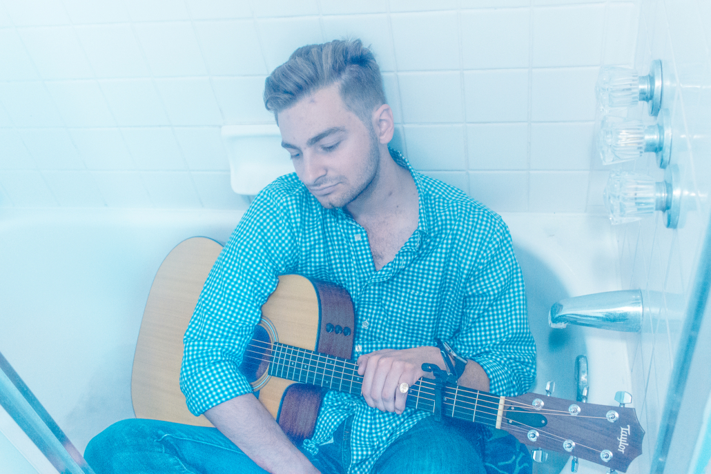Jack Henry sits in a bathtub with a guitar in his hand.