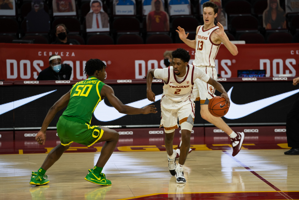 Redshirt-senior Tahj Eaddy dribbles the ball away from an Oregon guard.