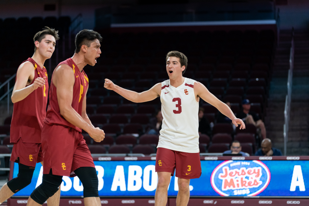 Cole Paxson (white) and other USC men's volleyball players cheering in a game.