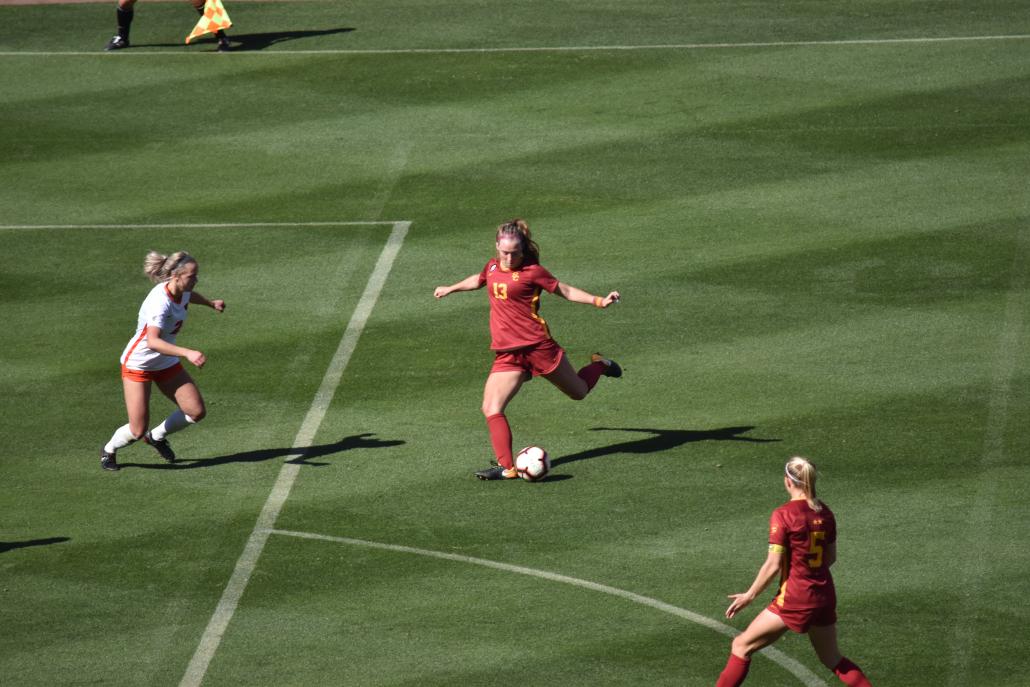 Senior forward Tara McKeown kicking outside of the box as a defender approaches.