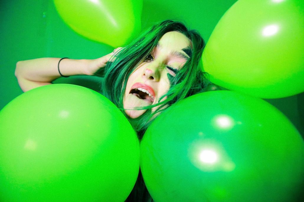 Green balloons surrounding Virgin Records artist, Phem.