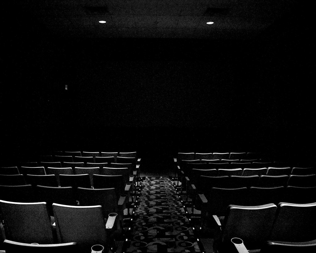 A black-and-white photo of empty rows at a movie theater.