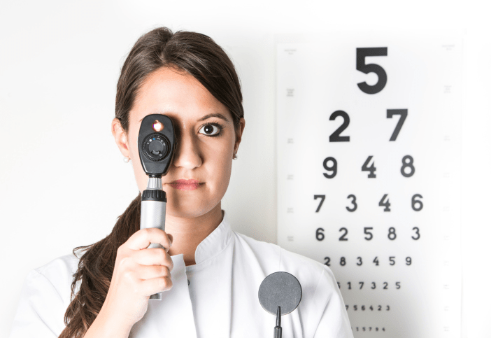 An optometrist holding retinascope in front of eye chart