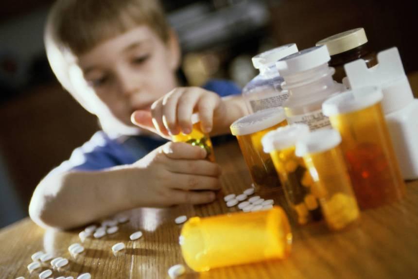Boy opening a pill bottle