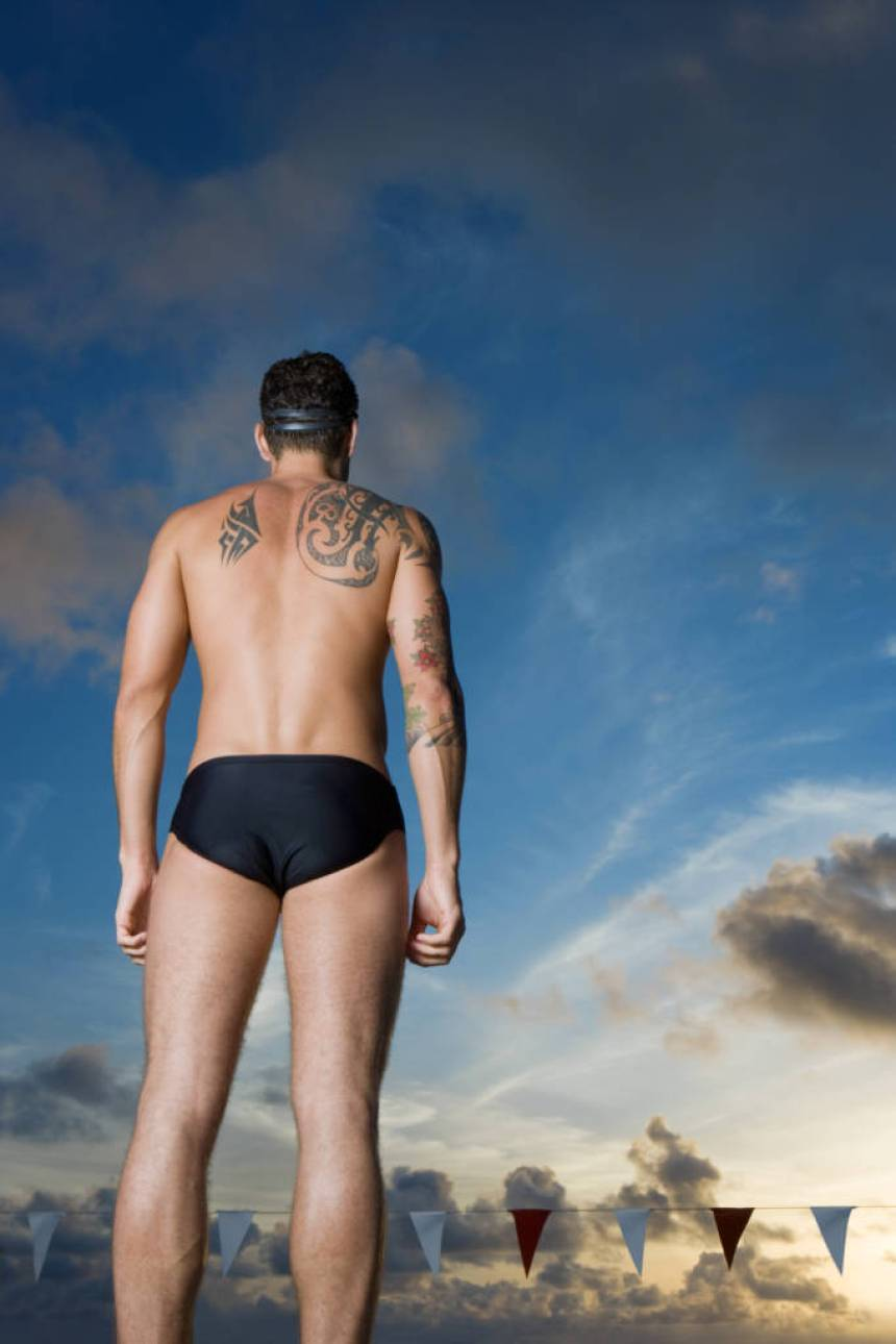 male swimmer with tattoo