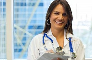 Female doctor smiles with a clipboard in hand