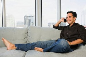 A man talking on the phone while sitting on his sofa