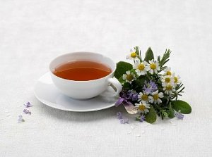 Tea cup and saucer with tea leaves and flowers