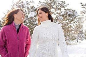 Two women walking outside in winter wearing sweaters