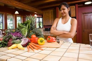 A woman stands beside a counter top with fresh vegetables