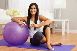 A woman leaning on a purple exercise ball at home