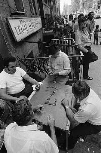 Black and white picture of men sitting outside playing dominoes