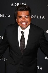 George Lopez stands in front of a step and repeat in a black suit