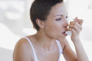 Young woman in white tank top uses inhaler