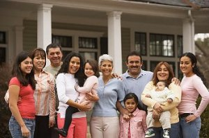 Multi-generational Latino family poses for picture in front of house