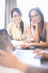 Latinas sit around a conference table working together