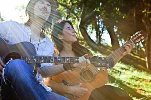 Couple sit outside singing with guitars in the sun