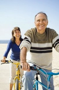 An older couple rides their bikes on the beach
